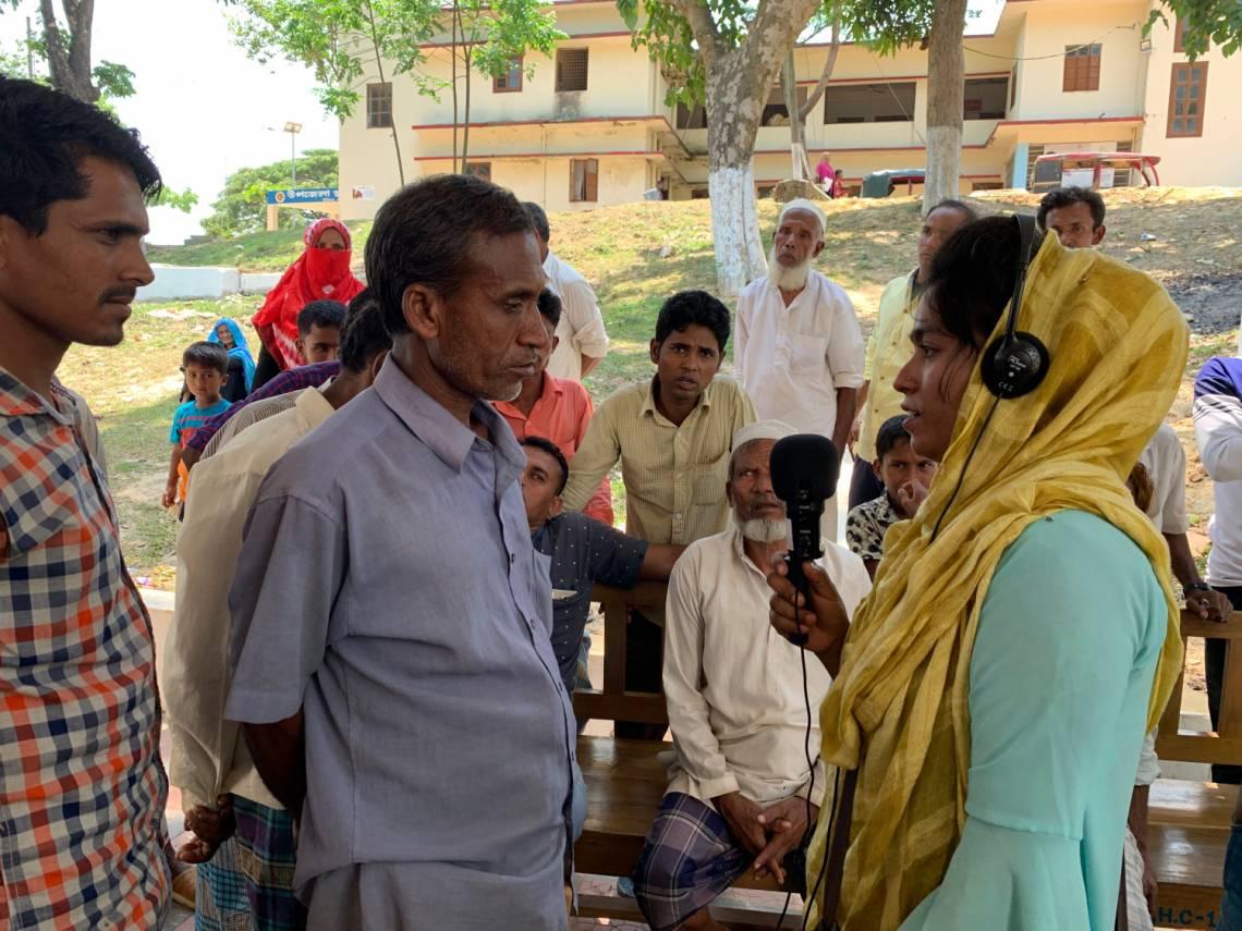 Une femme bangladaise de la communauté d'accueil en train de réaliser une interview