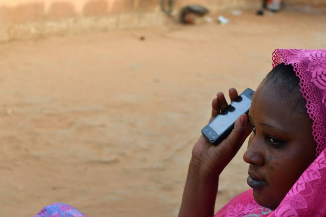 A women listening to Studio Kalangou on her smartphone in Niamey, Niger.