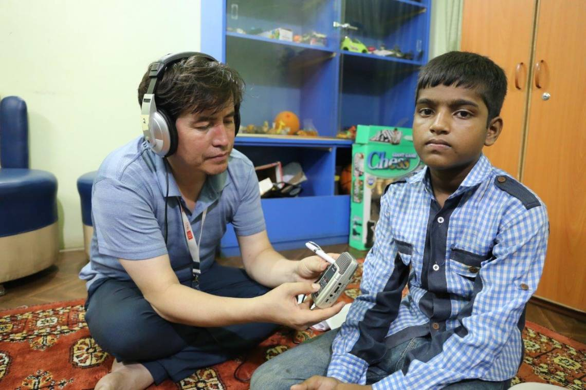 An Afghan participant to the workshop interviewing a child for an audio documentary, on July 18, 2017 in Karachi.