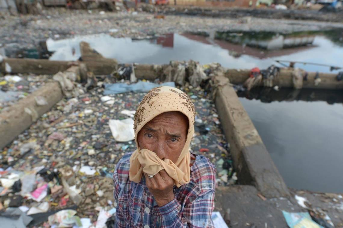 Une mère de famille indonésienne devant un barrage rempli d'ordures à Jakarta, en 2013.